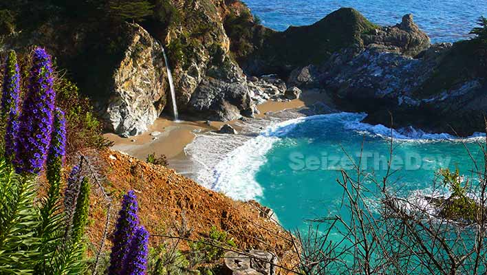 Big Sur California, Mcway Falls Waterfall pours onto a serene beach which washes away into the Pacific Ocean.